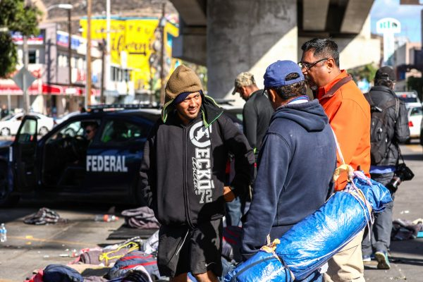 Marco Gómez (L) and several other Honduran migrants slept under a bridge across the road from the Chaparral port of entry to the United States in Tijuana, Mexico, on Nov. 23, 2018. (Charlotte Cuthbertson/The Epoch Times)